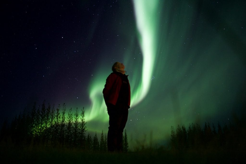 My wife Danielle and the Northern Lights near Geysir in Iceland.  She took this one herself using a self-timer while I was passed out sick in our hotel room.